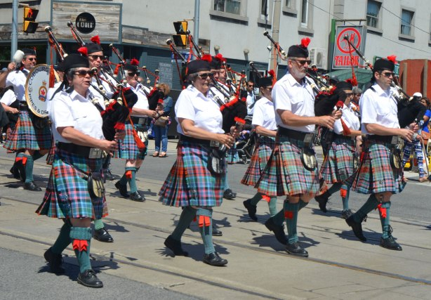 members of the Cobourg Legion pipe and drum band, four bagpipers in their blue and red kilts marching in a parade