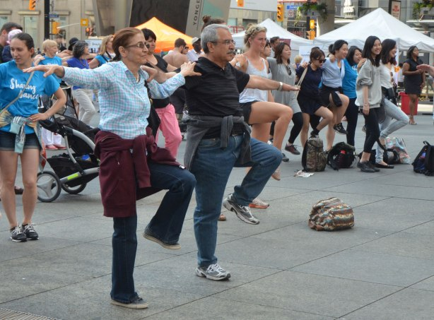 people dancing at Yonge Dundas Square as a group, part of an event called Sharing Dance - a middle aged couple