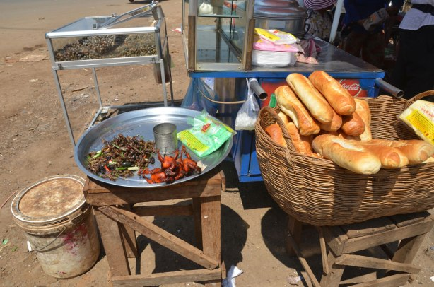 a roadside food stand in Cambodia, selling bbq rats, deep fried crickets, baguettes and snails