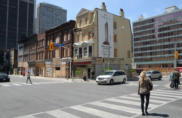 Looking across the intersection of Yonge and Yorkville streets at a row of old three storey brick stores that now have their doors and windows boarded up.