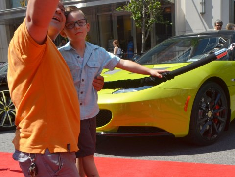 A father is taking a selfie of himself with his son in front of a yellowish green sports car at a car show.