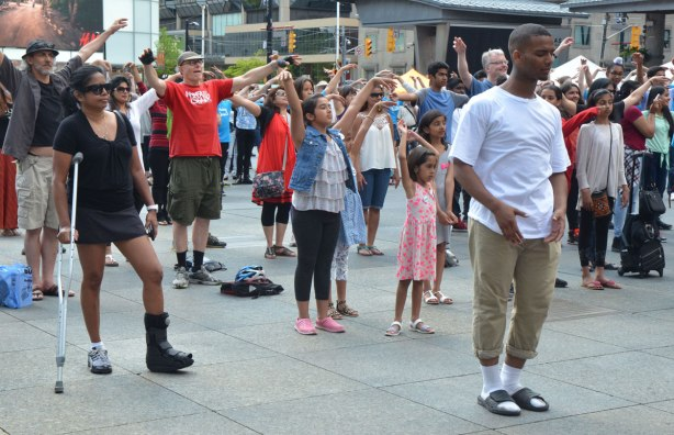 people dancing at Yonge Dundas Square as a group, part of an event called Sharing Dance - hands in the air