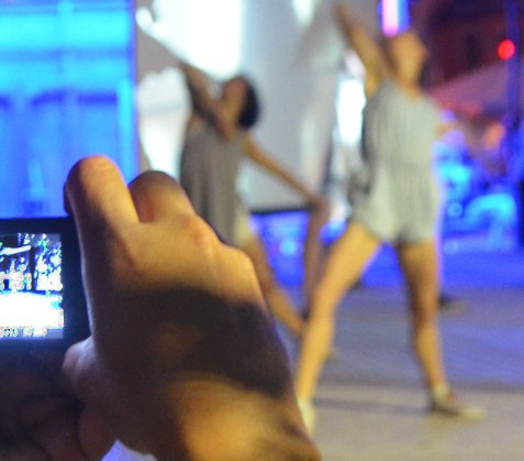 a hand holding a camera, two dancers out of focus in the background.