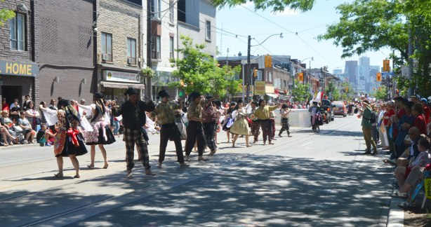 On a street, Dundas West in Toronto, there is a parade, people on the sidewalk watching, and dancers performing in the parade. Portugal Day parade.