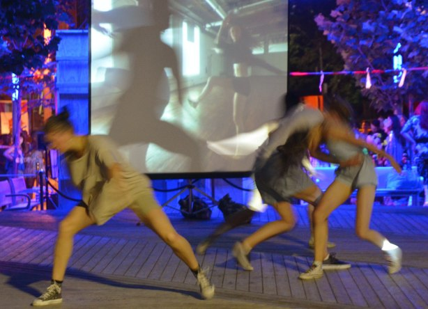 Dancers performing in front of a video playing on a screen, night time performance, some of the dancers are partly blurry