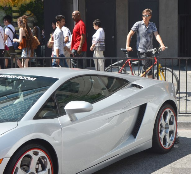 A young man holding his bike stands behind a metal fence while looking at a grey sports car at an outdoor car show in Yorkville