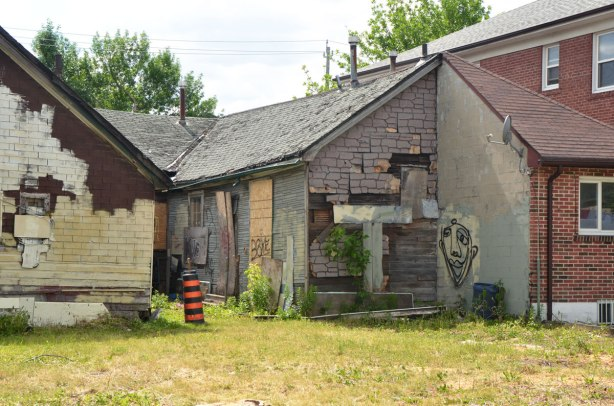 backyard, and back of an old building that has been boarded up. The ashphalt shingles on the back of the building are torn , there is a graffiti face painted on one wall