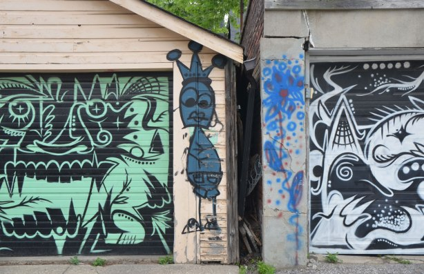 a skinny blue graffiti figure on the edge of a garage, between two garage doors with stylized and abstract faces painted on them. One is black and green and the other is black and white