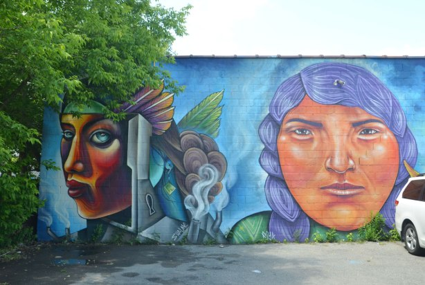 two faces, mural, painted on the side of building, both women, a multicoloured face in profile by Shalak on the left and a woman with purple hair by Fiya on the right.