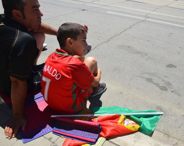 A boy is wearing a Rinaldo soccer shirt, and sitting beside a Portuguese flag. His father is with him
