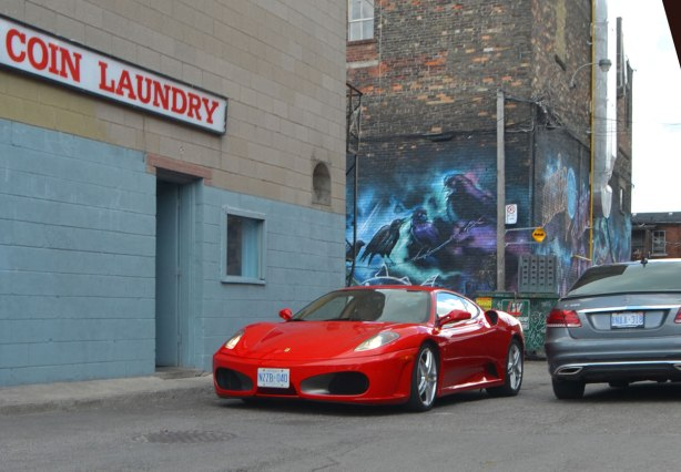 a red Ferrari and a beige Mercedes drive past each other beside a coin laundry in a lane.