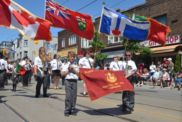 Two boys holding a red banner for a marching band in a parade. Lots of flag holders behind them, a Canadian flag, an Ontario flag, a Toronto flag and a Portuguese flag.