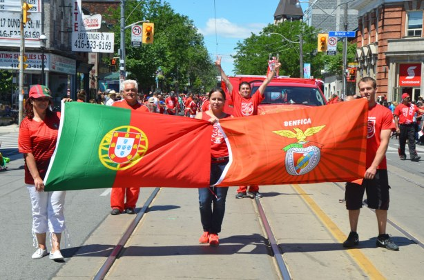 People in a parade, three people holding two flags, Portugal and Benfica. A man behind them is holding his arms up in the air.