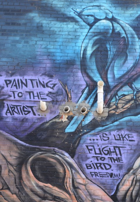 "part of mural, a dark blue bird sits in a tree. The words ""Painting to the artist is like flight to the bird. freedom"""