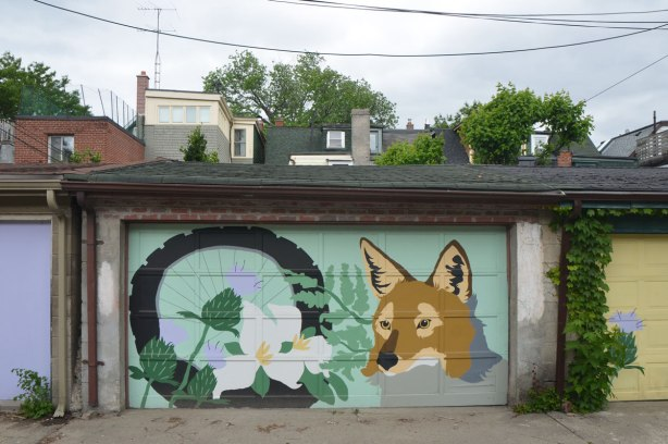 garage door in an alley painted with a mural of a fox head beside a bicycle wheel with trilliums growing up in front of it.