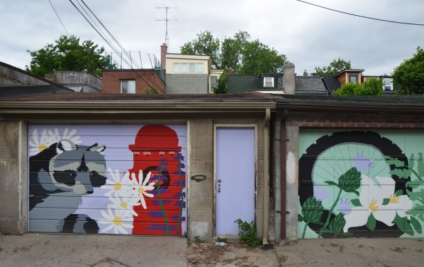 view in an alley, a lavendar coloured door. to the left of the door is a garage door painted with a mural of a raccoon and a red fire hydrant.