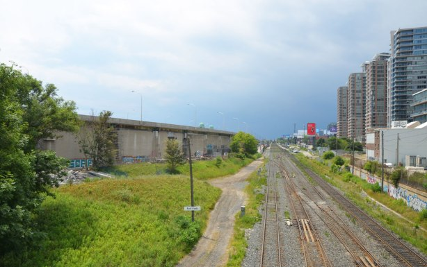 railway tracks in the center of the picture, condos on the right. On the left is the elevated Gardiner expressway, but under it is a concrete wall that makes it look more like a concrete building than a road