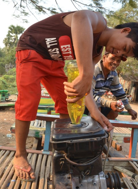 A boy fills an engine with yellow coloured gas that was in an old plastic pop bottle