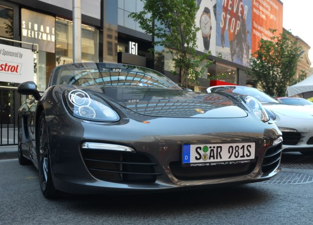 A dark grey Porsche with German licence plates is parked on Bloor Street, beside an older white Porsche, for the 6th annual Yorkville exotic car show.