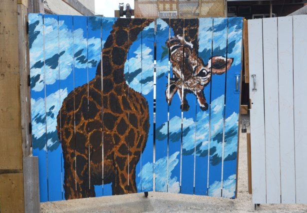 graffiti street art animals painted on garage door in an alleyway - a giraffe against blue sky with clouds. It's head is bent down so that the giraffe fits in a square space