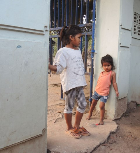 two little girls standing in a doorway, entrance to a courtyard