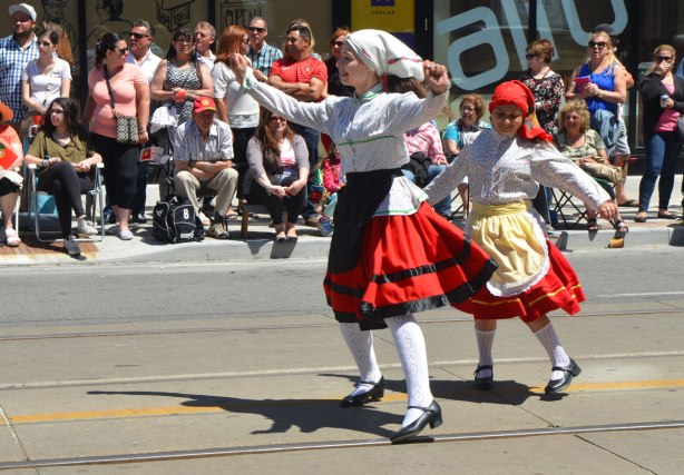 Two girls in traditional Portuguese dresses are dancing in a parade, onlookers sitting on the sidewalk behind them.