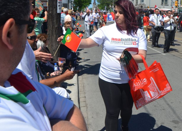 A woman is giving out small portuguese flags to people watching a parade. She is wearing a t-shirt in support of local politician Anna Bailao,