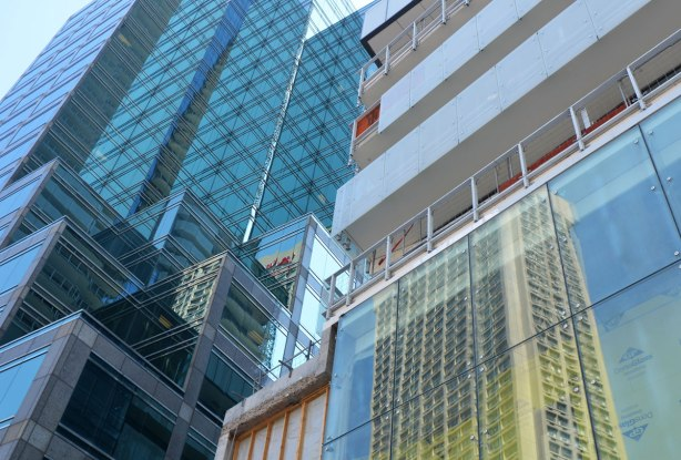 part of a glass wall of windows of a tall condo under construction - parts of two adjacent buildings
