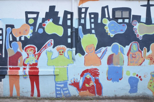 Part of a mural in an alley painted by students from Gledhill Public school, graduating class of 2009, black silhouette of the Toronto skyline with big colourful footprints, some roughly drawn people too