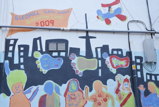 Part of a mural in an alley painted by students from Gledhill Public school, graduating class of 2009, black silhouette of the Toronto skyline with big colourful footprints, some roughly drawn people too , an airplane flies overhead