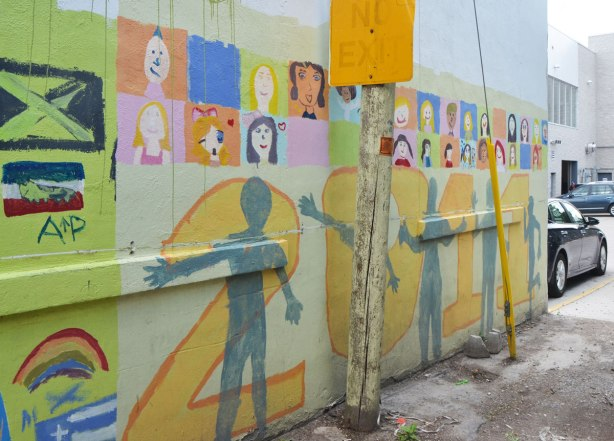 Part of a mural in an alley painted by students from Gledhill Public school, graduating class of 2011. 2011 in large numbers across the bottom with grey silhouettes of people, brightly coloured squares with faces across the top