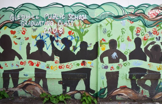 Part of a mural in an alley painted by students from Gledhill Public school, graduating class of 2008, black silhouettes under tree branches, hand prints too
