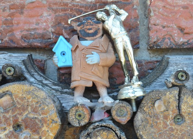 garage in a laneway decorated by Albino Carreira using slices of wood, pool cues, toy figures, and small found objects - detail of one section, a gold figurine of a golfer, a fat man holding a blue birdhouse