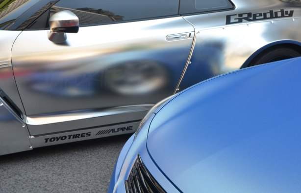 parts of two cars parked beside each other in a car show, one is blue and the other is silver. The front wheel of the blue car is reflected in the side panel of the silver car which has G Reddy painted by the rear window.