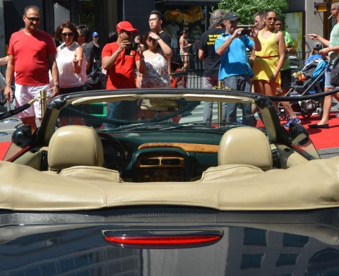 dark green convertible in the foreground, people looking at in the background