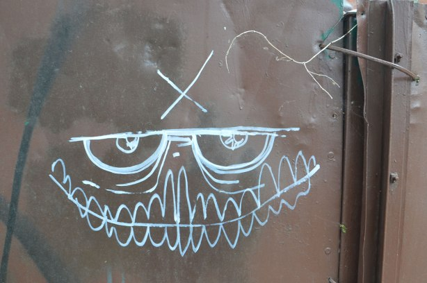 On a brown metal door, a white line drawing of a grinning face with many teeth and semi circular eyes