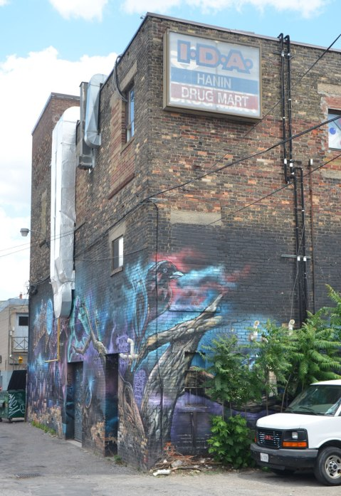 brick building in a laneway. At the top is an old sign that says IDA Hanin Drug Mart. Below, a large mural with birds.