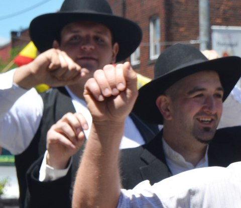 Close up shot of the hands of three men dancing in a parade. The faces of only 2 of them are visible. They are wearing white shirts, black vests, and black hats. Portugal Day parade