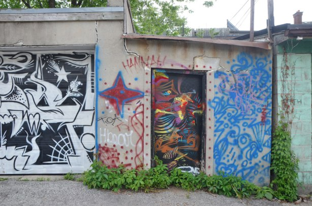 An old garage and concrete fence with a door in it. The fence is cracked above the door. The door is painted black with bright colour scribbles, the garage door has a black and white mural on it