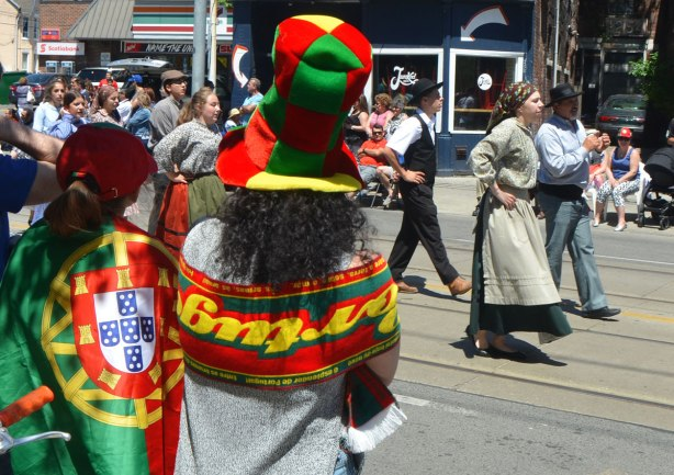 A young woman is wearing a large tall hat in squares of the colours of the Portuguese flag. Beside her is a person draped in the Portuguese flag. They are watching a parade