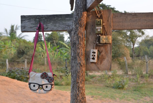 A hello Kitty purse hangs from a piece of wood beside 4 small electrical boxes with switches and outlets