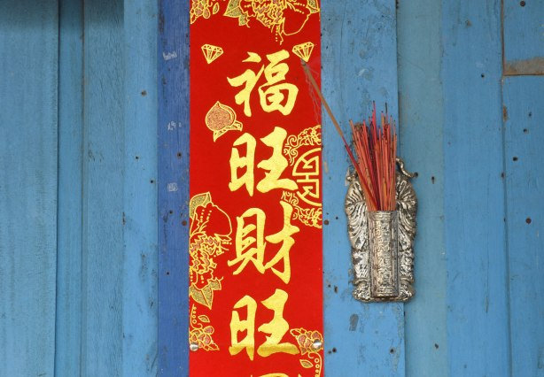 A blue wood door, a red banner with gold Chinese lettering, and a silver holder for incense sticks, many reddish incense sticks in it