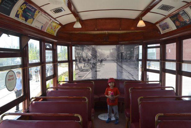A young boy stands in the back of an old restored ttc streetcar. A black and white picture of an old street scene has been put across the back window to show you what the view out the window might have looked like at the time the streetcar was functional. Old ads on the upper part of the interior, wood trim
