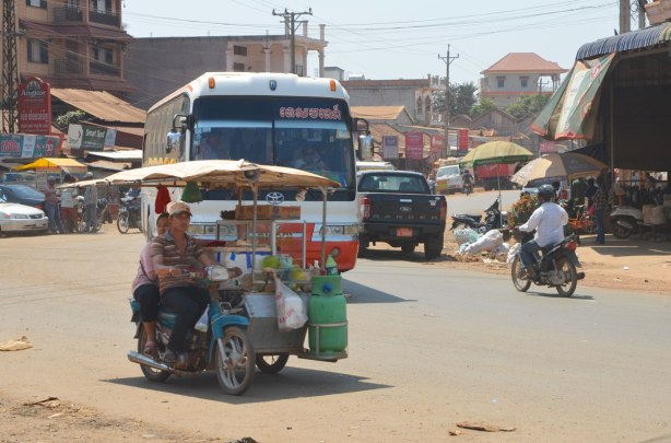 at a busy intersection, a Cambodian bus, a motorcyle with sidecar laden with goods as well as two people