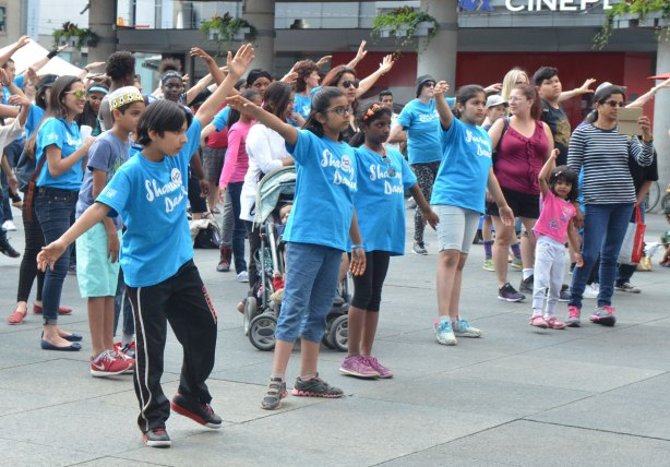 people dancing at Yonge Dundas Square as a group, part of an event called Sharing Dance - kids