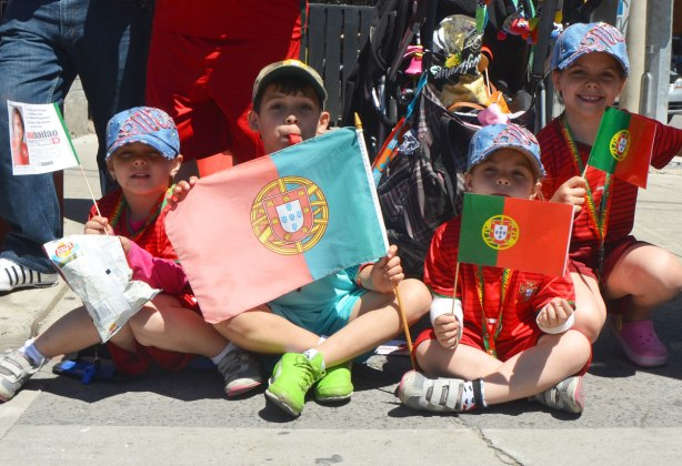 Four kids sitting crossed legged at the side of a street watching a parade. They are holding Portuguese flags. The older boy has a red whistle in his mouth.