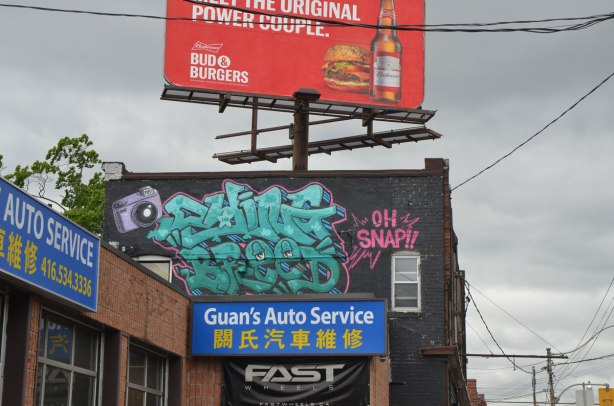 Above Guan's auto service shop, a graffiti on an upper storey wall, a small camera and turquoise lettering and words in pink that say Oh snap. Above that is a red billboard for Bud and Burger