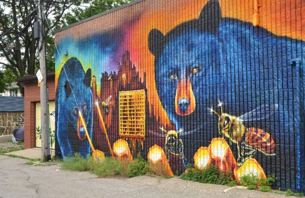 large mural by Nick Sweetman on a wall in Frank Kovac Lane, two very large blue bears are eating honey from honeycombs while a few large bees buzz around.