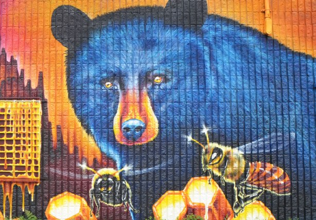 part of a large mural by Nick Sweetman on a wall in Frank Kovac Lane, two very large blue bears are eating honey from honeycombs while a few large bees buzz around - close up of one bear's face