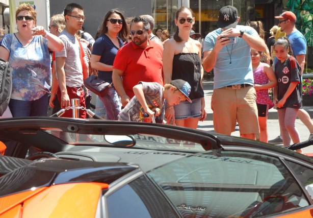 people looking at, and taking pictures of, a black and orange Lamborghini at a car show, outdoors, Yorkville
